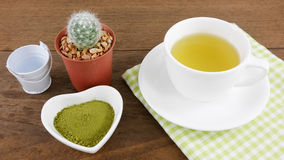 The Japanese matcha green tea powder on ceramic heart shaped bowl and cup of hot green tea with cotton fabric Royalty Free Stock Image