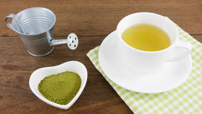 The Japanese matcha green tea powder on ceramic heart shaped bowl and cup of hot green tea with cotton fabric Royalty Free Stock Photography