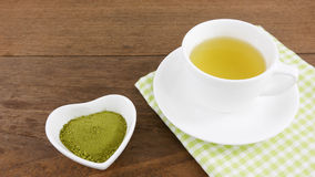 The Japanese matcha green tea powder on ceramic heart shaped bowl and cup of hot green tea with cotton fabric Royalty Free Stock Photos