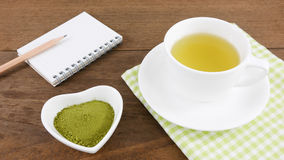 The Japanese matcha green tea powder on ceramic heart shaped bowl and cup of hot green tea and note book with pencil Stock Images
