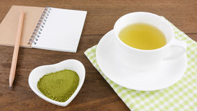The Japanese matcha green tea powder on ceramic heart shaped bowl and cup of hot green tea and note book with pencil Stock Photography
