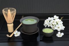 Japanese Matcha Tea. Japanese green matcha tea with cup, whisk, scoop, powder and cherry blossom on black tray background. Health drink concept stock photography