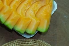 Japanese melon slide fruit background. On wood table Stock Image