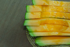 Japanese melon slide fruit background. On wood table Stock Photos