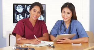 Japanese and Mexican medical doctors smiling at desk Royalty Free Stock Image