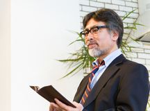 Japanese middle-aged man in suit reading book Royalty Free Stock Photo