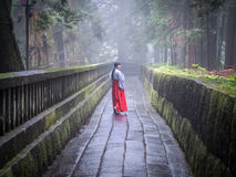 Japanese Miko on Path. A Japanese Miko Shrine Maiden walks down a Cedar lined path in the misty hills of Nikko, Japan Royalty Free Stock Photo