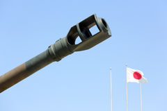 Japanese military cannon. With japanese flag against a blue sky Stock Photography