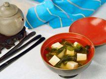 Japanese miso soup. With chopsticks and teapot on white table with blue napkin Stock Image