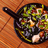 Japanese miso soup in a black bowl on bamboo napkin. Stock Photography