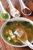 Japanese miso soup in bowl with a spoon horizontal. Japanese miso soup in a white bowl with a spoon on a table close-up. horizontal Royalty Free Stock Photos