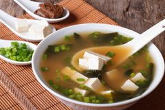 Japanese miso soup in bowl with a spoon vertical. Japanese miso soup in a white bowl with a spoon on a table close-up. vertical Royalty Free Stock Images
