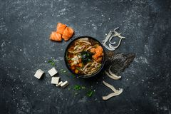 Japanese miso soup with tofu and salmon in a black bowl on a vintage colored background with ingredients. Top view Royalty Free Stock Image