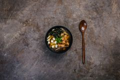 Japanese miso soup with tofu and salmon in a black bowl on a vintage colored background with a wooden spoon. Top view Stock Photography