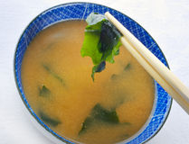 Japanese miso soup with Wakame. Flakes.  Focus on chopstick end Stock Image
