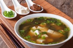 Japanese miso soup in a white bowl and ingredients close-up. Hor. Japanese miso soup in a white bowl and ingredients in a spoon on a table close-up. horizontal Royalty Free Stock Photo