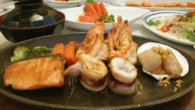 Japanese mixed seafood. Fried salmon, squid, shrimp, shell with clear soup Royalty Free Stock Image