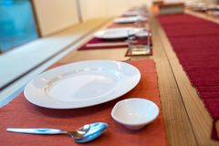 Japanese modern applied dining room style with eastern dish, fork, spoon, napkin and glass on the table royalty free stock photography