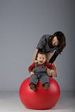 Japanese mom and son playing. Portrait of a japanese mother and toddler son playing on a pilates pall Stock Photography