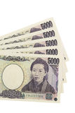 Japanese Money. A spread of five 5,000 yen notes on a white background. The yen is used in Japan, the world's second largest economy stock photos
