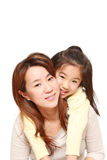 Japanese mother giving her daughter piggy back Royalty Free Stock Images