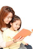 Japanese mother reading a book to her daughter Stock Photography