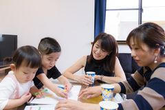 Japanese fellow mom and children having food party and enjoying drawing at home royalty free stock photos