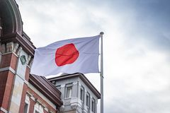 Japanese national flag in Japan national day in windy and cloudy day in front of Tokyo train station.  royalty free stock photo
