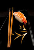 Japanese nigiri sushi, chopsticks, black plate. Japanese nigiri sushi with rice and prawn and chopsticks on a black Japanese plate Stock Photography