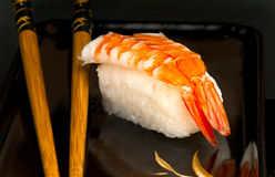 Japanese nigiri sushi with prawn. Japanese nigiri sushi with rice and prawn and chopsticks on a black Japanese plate Royalty Free Stock Photos