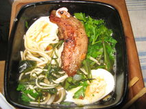 Japanese noodle soup with pork rib. Color digital photo of japanese noodle soup with pork rib roasted in soy sauce hardboiled egg algae and fresh parsley Stock Photo