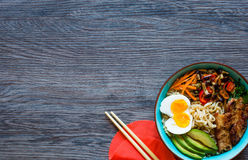 Japanese noodles bowl with chicken, carrots, avocado Royalty Free Stock Image