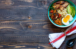 Japanese noodles bowl with chicken, carrots, avocado Royalty Free Stock Photos