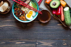 Japanese noodles bowl with chicken, carrots, avocado Royalty Free Stock Photo
