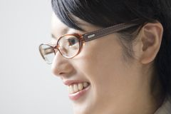 Japanese office lady. Close-up portrait of young smiling business woman wearing glasses with head set Stock Photo