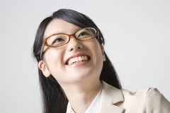 Japanese office lady. A young smiling Japanese woman with glasses on light gray background Stock Image