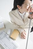 Japanese office lady. A young Japanese woman sitting at her desk and speaking on the phone with smile Royalty Free Stock Photo