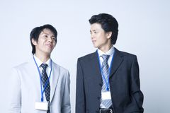Japanese office workers. Two young Japanese businessmen standing like partners and talking Stock Photo