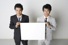 Japanese office workers. Young Japanese businessmen with a whiteboard and gray background Stock Photography