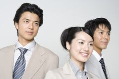 Japanese office workers. A businesswoman and two businessmen standing together Royalty Free Stock Photos