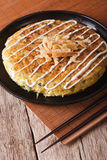Japanese okonomiyaki on a table close-up and chopsticks. vertica Stock Photo