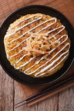Japanese okonomiyaki on a table close-up. vertical top view Stock Photos
