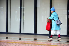 Japanese old woman wear raincoat walking while raining time Royalty Free Stock Image