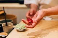 Japanese Omakase chef making Chutoro Sushi Medium Fatty Bluefin Tuna neatly by hands. Japanese traditional, authentic and luxury stock photography