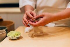 Japanese Omakase Chef making Chutoro Sushi Medium Fatty Bluefin Tuna, pasting fresh wasabi neatly by hands. royalty free stock image