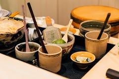 Japanese Omakase Ingredients: Steel peel scraper, wooden sauce brushes in ceramic cups. Japanese luxury meal.  stock image