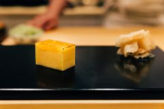 Japanese Omakase meal: Tamakoyaki sweet egg custard in block shape served by hand with pickled ginger on glossy black plate. Japanese traditional and luxury stock photo