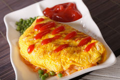 Japanese Omurice with rice, peas and ketchup close-up, horizonta Royalty Free Stock Image