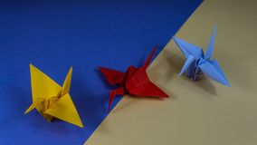 Japanese origami. Origami crane is a symbol of peace. Three cranes on blue and yellow background stock image