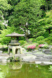 Japanese outdoor stone lantern, flower plants in zen garden Stock Photo